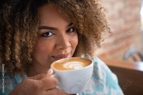 Fotografija woman drinking coffee with playfull gaze