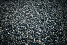 Closeup Of A Rocky Shore At The Beach With Gray Pebbles Illuminated By Sunlight