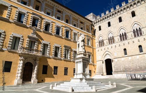 Naklejka premium Monument to Sallustio Bandini and Palazzo Salimbeni in Siena, Italy