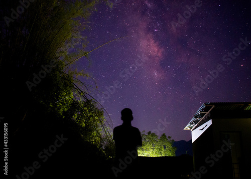 Fotografie, Obraz Night time picture of man standing in front of bright milky way