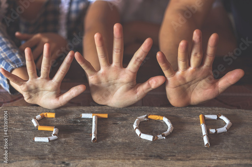 Fototapeta The word stop spelled using cigarettes on wooden background with stop hands