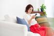 Leinwandbild Motiv スマートフォンを使っている妊婦の女性