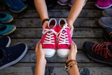 Shoes At The Hands Of Two Women