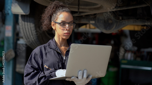 Stampa su Tela african american mechanic woman using laptop computer  checking list to undercarriage of car in workshop at auto car repair service center with lift