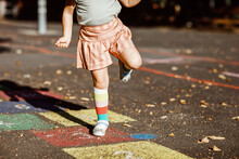 Closeup Of Leggs Of Little Toddler Girl Playing Hopscotch Game Drawn With Colorful Chalks On Asphalt. Little Active Child Jumping On Playground Outdoors On A Sunny Day. Summer Activities For Children.