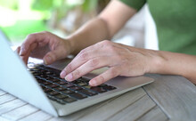 Woman's Hands Typing On Computer Keyboard. Close Up View. Outdoor Or Garden Background.