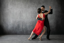 Couple Of Professional Tango Dancers In Elegant Suit And Dress Pose In A Dancing Movement On Dark Background. Attractive Man And Woman Dance Looking Eye To Eye.