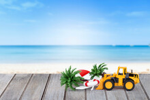 Summer Season Background Idea, Yellow Front Loader Truck With Beach Item Over Blurred Beach Background, Outdoor Day Light