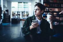 Pensive Man With Takeaway Coffee Using Smartphone