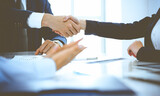 Fototapeta Kawa jest smaczna - Businesspeople or lawyers shaking hands finishing up a meeting in blue toned office , close-up. Success at negotiation and handshake concepts