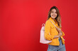 Leinwandbild Motiv Happy woman with backpack on red background. Space for text