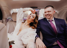 The Bride And Groom In The Back Seat Of The Car. Renting A Car For A Wedding.