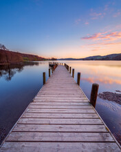 Sunset At A Wooden Jetty On Coniston Water In The English Lake District With A Colourful Sky