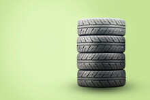 A Set Of New Summer Tires On A Green Background. Economical Modern Quiet Tires, Empty Copyspace Space