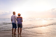 An Elderly Asian Couple Stand Together On The Beach Look At The Beautiful Sea In The Morning Together. Travel Concept To Live Happily In Retirement Age. Copy Space