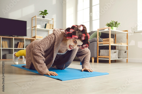 Fotografía Young woman exercising on fitness mat and smiling