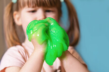 A Small, Cute Girl Is Holding A Green Slime On A Blue Background. A Child Plays With A Slimy Toy At Home. Chewing Gum In Children's Hands. Children Play. Family Fun. Games For Children And Adults.