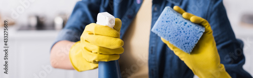 Fototapeta Cropped view of woman in rubber gloves holding detergent and blurred sponge, banner obraz