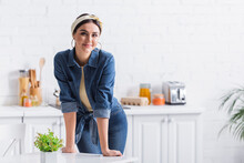 Smiling Housewife In Headband Looking At Camera Near Kitchen Table