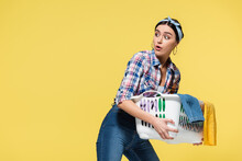 Surprised Housewife Holding Basket With Clothes And Looking Away Isolated On Yellow
