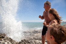 Father With Children Looking At Water Splash While Standing On Rock
