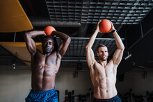 Muscular Male Athletes Holding Sports Ball While Exercising In Health Club