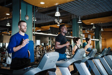 Male And Female Sports People Exercising On Treadmill In Health Club