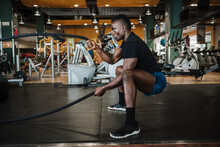 Muscular Sportsman Exercising With Rope During Sports Training In Gym