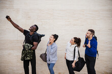 Cheerful Athlete Friends Taking Selfie Through Smart Phone By Wall