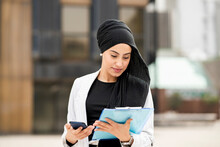 Young Businesswoman With Smart Phone Looking At Strategy Outdoors