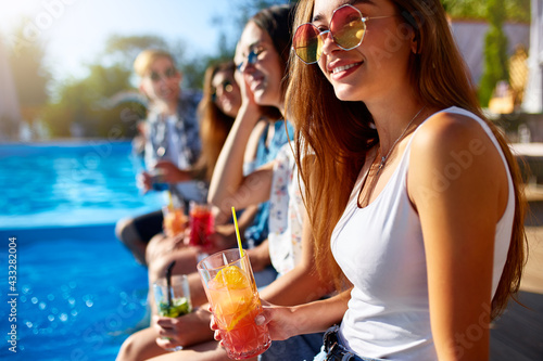Pretty woman relax with fresh colorful cocktail glass sitting by swimming pool on sunny summer day with friends Fototapeta