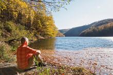 Senior Man Relaxing On Shore Of Rursee Reservoir In Autumn