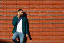 Smiling Young Man Talking On Mobile Phone While Leaning On Wall