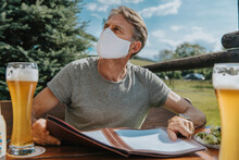 Man With Protective Face Mask Ordering Food While Looking Away In Beer Garden