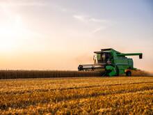 Combine Harvesting Field Of Wheat At Sunrise