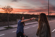 Cheerful Female Friends Punching Fists On Road
