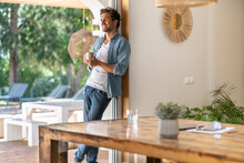 Happy Relaxed Man Holding Coffee Cup While Leaning On Doorframe At Home
