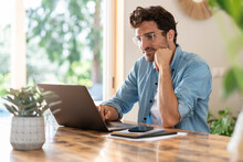 Serious Male Freelancer With Head In Hands Working On Laptop At Home Office