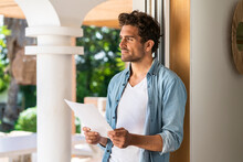 Thoughtful Man Looking Away While Holding Bill At Doorframe