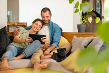 Man Embracing Woman Holding Digital Tablet While Sitting With Pug Dog On Sofa At Home