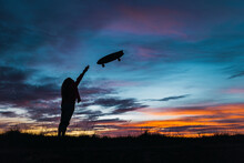 Woman In Silhouette Throwing Skateboard In Front Of Sky During Sunset