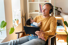 Smiling Father Listening Music While Holding Sleeping Baby And Digital Tablet In Living Room