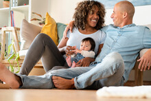 Happy Family With Daughter Sitting On Floor In Living Room