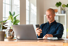 Smiling Businessman With Laptop Using Mobile Phone While Working At Home