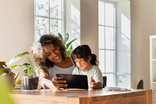 Smiling Mother And Daughter Looking At Digital Tablet While Sitting In Living Room