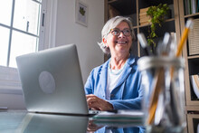 Happy Businesswoman Looking Away While Working With Laptop At Home