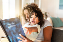 Toddler Girl Gesturing While Mother Reading Book To Her In Living Room