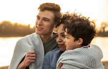 Family Covered In Blanket Together During Sunset