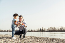 Young Man And Boy Checking Airplane Toy By Lake