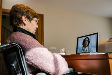 Disabled Senior Woman On Video Call With Female Doctor At Home